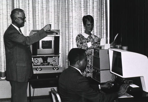 <p>Two men and a woman are in a room with microfilm readers.</p>