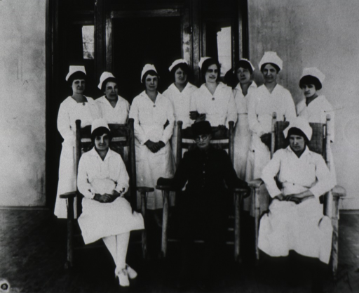 <p>Nurses posed for group photo; three are sitting, one of which is wearing a dark uniform, others are standing and wearing white uniforms.</p>
