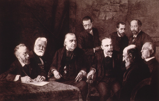 <p>Seated at table, head to right, surrounded by eight men.</p>