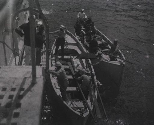 <p>View of staff taking wounded from two boats.</p>