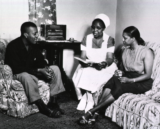 <p>Showing Sadie Nickpeay counselling African American parents in their home from a book on pre-natal care.</p>