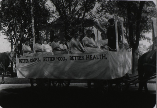 <p>Horse-drawn wagon on which several women are seated; a banner hanging over the side reads: Better Cooks, Better Food, Better Health.</p>