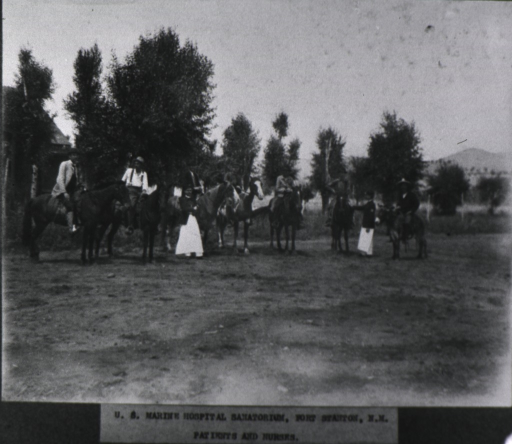 <p>Several men are sitting on horseback; two men standing on the ground are wearing military jackets over white aprons.</p>