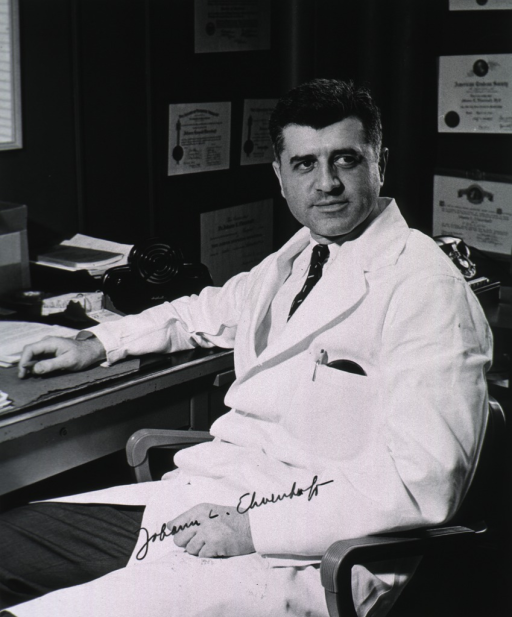 <p>Three-quarter length, full face, seated at desk, wearing white coat.</p>
