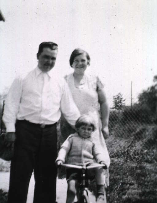 <p>A mother and father stand behind a child on his tricycle.</p>