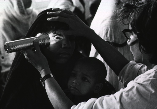 <p>A young mother is having her eyes examined by a physician using a flashlight; the mother is holding a child in her lap.</p>