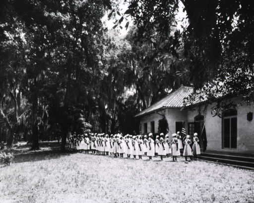 <p>Showing the African American midwife students beginning the day with a formal march into the general session.</p>