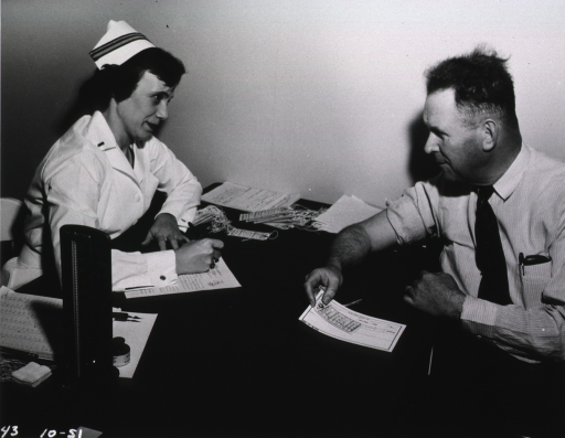 <p>A man sits at a table with his right shirt sleeve pulled up.  In his left hand he holds forms.  A female nurse sits across from the man and writes on a form.</p>