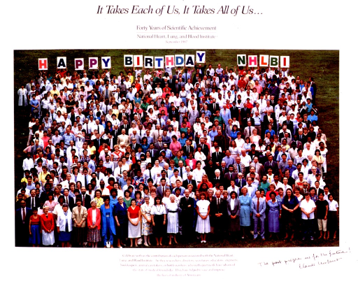 <p>A large group of people is standing on a grassy lawn, holding up letters that spell out &quot;Happy Birthday NHLBI.&quot;  In the bottom right corner the poster is inscribed &quot;The past prepares us for the future! Claude Lenfant.&quot;</p>