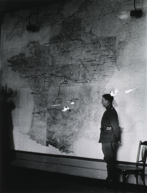 <p>Full length, left pose, standing before large wall map of France.</p>