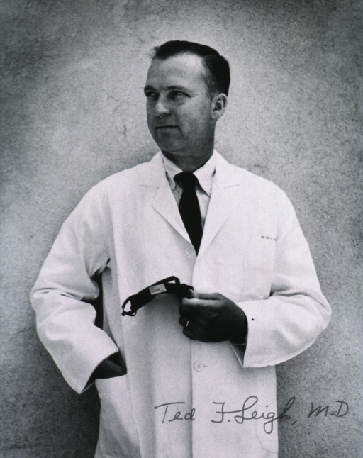 <p>Three-quarter length, standing, head turned to the right; wearing white coat, holding article in left hand.</p>