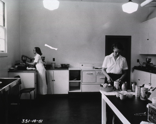 <p>Two women perform tasks in the kitchen of a blood donor center.  One of the women prepares coffee, while the other woman stands at a table and opens a can of pineapple juice.  Next to the can of pineapple juice is a plate of pastries.</p>