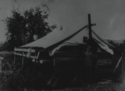 <p>A man in uniform standing in front of a 'tent-house' comprised of wooden sides and a canvas tarp overhead through which projects a stove pipe.</p>