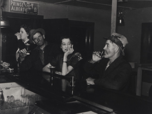 <p>Two men and two women sit at a bar drinking and smoking; a Prince Albert tobacco sign is on the wall in the background.</p>