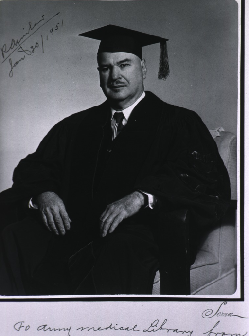 <p>Seated, full face, hands in lap, cap and gown.</p>