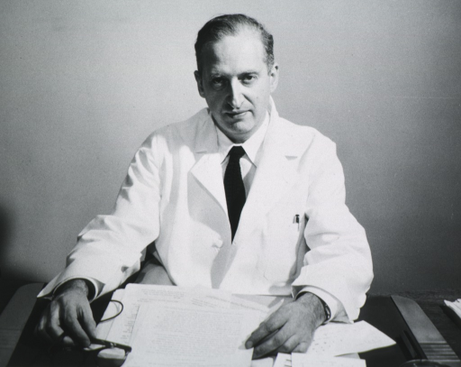 <p>Half-length, seated at desk, full face; wearing white lab coat.</p>