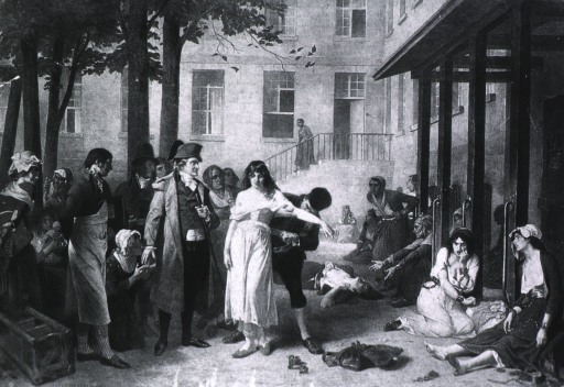 <p>Pinel stands in the courtyard as a woman patient is freed from her chains; other women patients are chained to wooden posts attached to a building.</p>