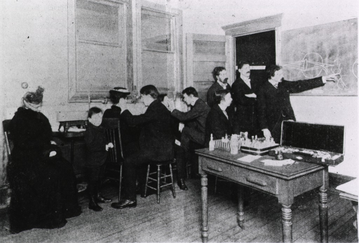 <p>Two medical students examine patients while four others discuss eye problems using a diagram on the chalkboard.  Medical supples are on a table nearby.</p>