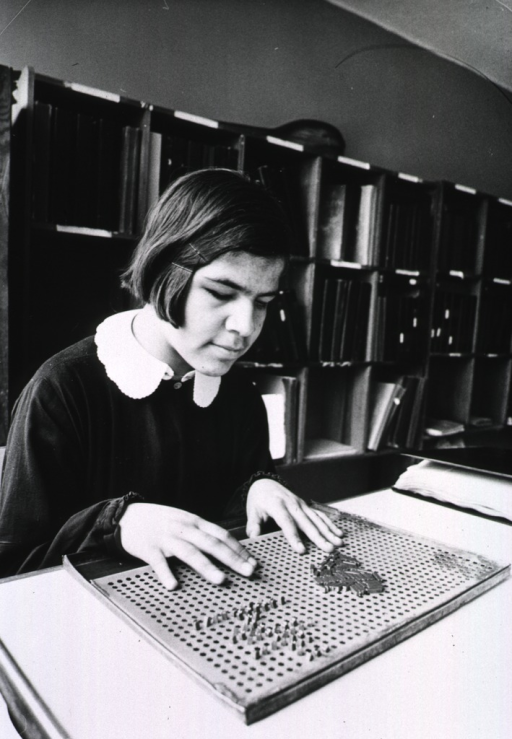 <p>A young girl is playing a game using pegs and a pegboard.</p>
