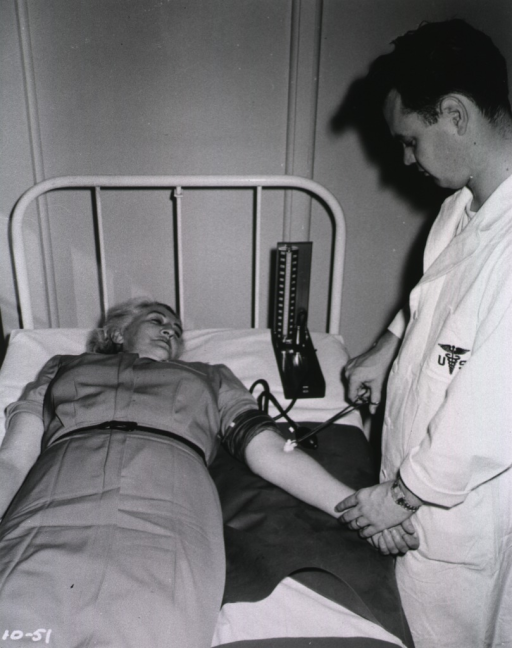 <p>A woman lies on a bed while a male medical staff member prepares to draw blood from her arm.  A sphygmomanometer is on the bed next to the woman.</p>