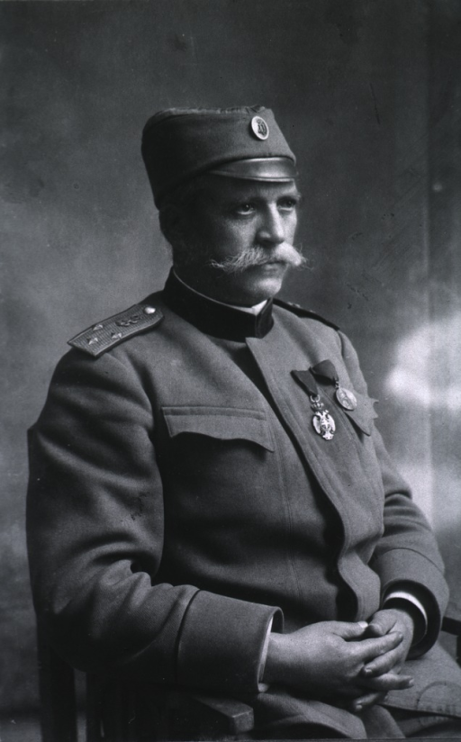 <p>Half-length, right pose, seated, hands together in lap; wearing uniform and cap.</p>