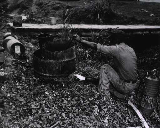 <p>Showing a construction worker preparing tar for waterproofing.</p>