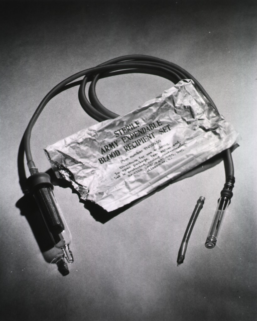 <p>Photograph of the blood recipient set and the wrapper from which it has been removed.  On the front of the wrapper are instructions and the name of the manufacturer (Baxtor Laboratories, Inc., Glenview Ill.).</p>