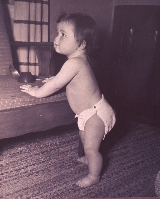 <p>Infant (full-length portrait, facing left) standing, supporting herself on a chair.</p>