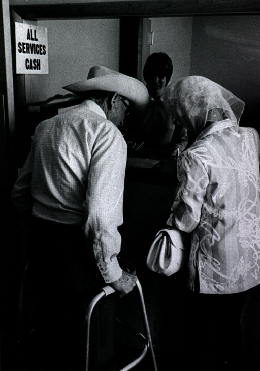 <p>Interior view: an elderly man using a walker and an elderly woman stand at the reception desk of the Martin Clinic; a young woman stands behind the desk; a sign &quot;All Services Cash&quot; is posted to the left.</p>