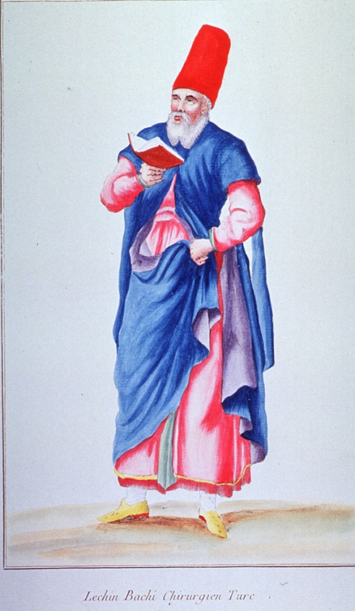 <p>Full length view of a Turkish surgeon, standing, holding a book, and wearing robes and a tall red fez.</p>