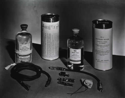 <p>The contents of the package of plasma, including a bottle of distilled water, a bottle of natural human plasma, tubes, and a clamp are displayed on a table.</p>