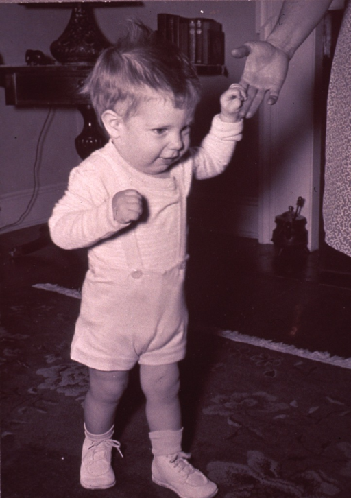 <p>Infant (full-length portrait, facing right) walking, supporting himself by grasping the fingers of an adult hand visible in the upper right.</p>