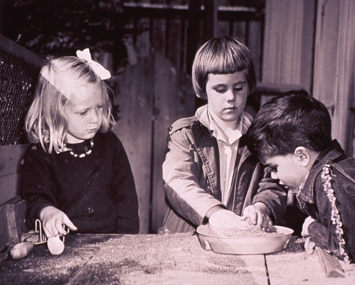 <p>Two girls and a boy are playing with sand.</p>