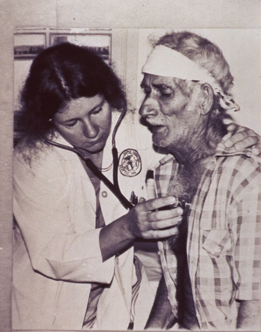 <p>Senior Assistant Surgeon Nancy Campbell examines an elderly man at the Fort Chaffee, Arkansas, Distribution Center; she listens to his chest sounds with a stethoscope.</p>