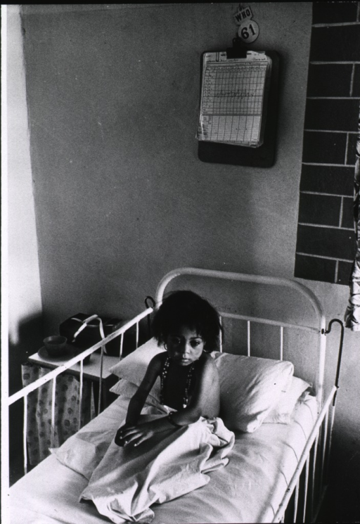 <p>Interior view: a young girl is sitting in a crib in a hospital in Jordan.</p>