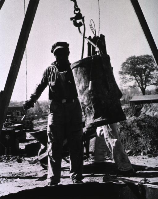 <p>Showing construction worker lowering materials.</p>