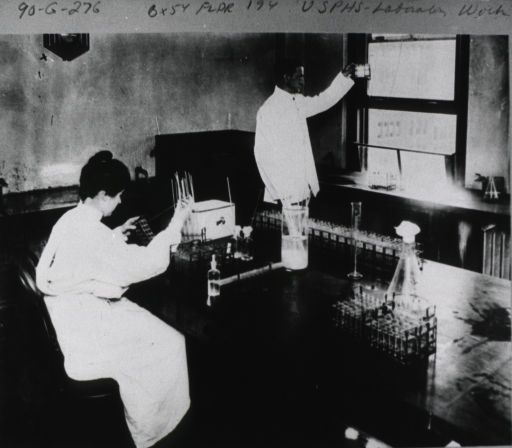 <p>Interior view of a laboratory: a woman sitting at a lab bench pipettes blood from a flask and transfers it to a test tube; a man standing at a window is holding an object up to the light.</p>