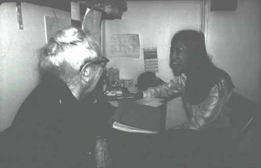 <p>A young woman and an elderly woman sit at a desk, they are laughing.</p>