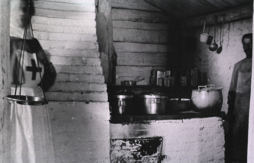<p>A nurse and staff person in the kitchen at Military Mobile Hospital No. 75.</p>