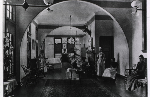 <p>Interior view of a long room furnished with several chairs and benches; two patients sit on the right and two nurses stand in the background.</p>