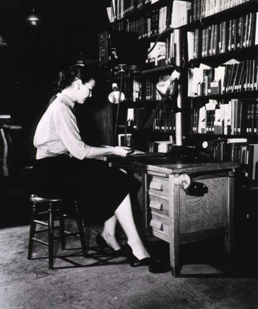 <p>Interior view:  A Kodak Recordak and flood lights are attached to a desk; filled book shelves are behind the desk.</p>