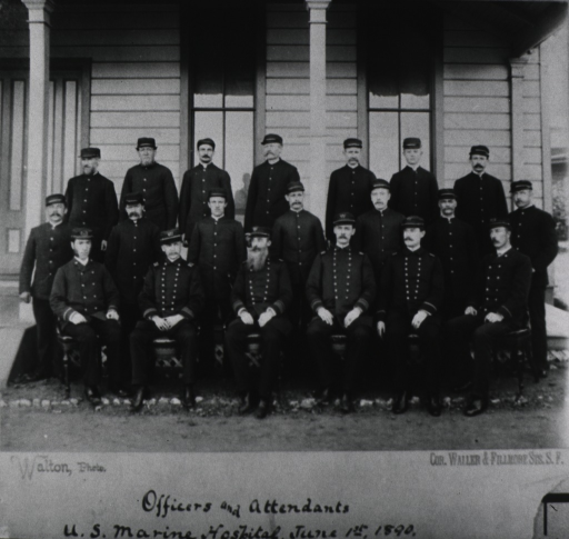 <p>Men in uniform posed for group photo in front of a building; front row is seated, second row is standing on the ground, and the third row is standing on a porch.</p>