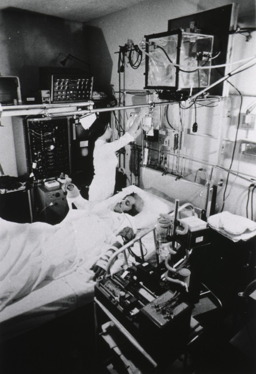 <p>Nurse adjusts intravenous flow of accident victim in trauma unit.  Physiological monitoring devices attached to patient are hooked up to computer.</p>