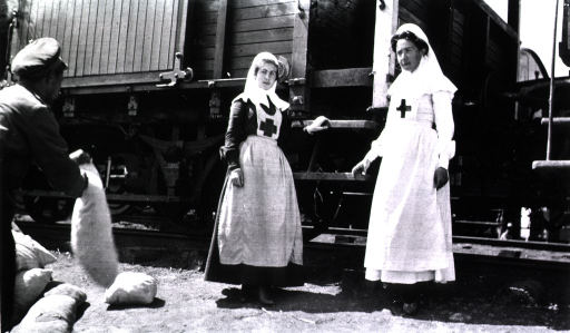 <p>Two nurses stand beside a train at the depot.  A man holding sacks is in the foreground.</p>