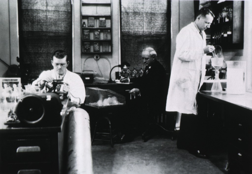 <p>In center of laboratory interior, seated at work bench.</p>