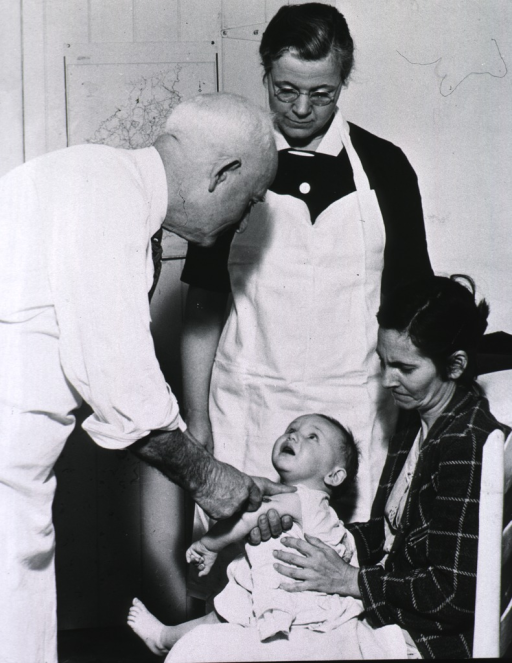 <p>An infant, sitting in his mother's lap, receives an injection from a doctor while Rosa Clark assists.</p>