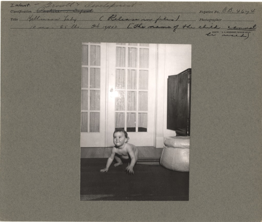 <p>Crouching infant attempting to raise herself up into a standing position (?).</p>