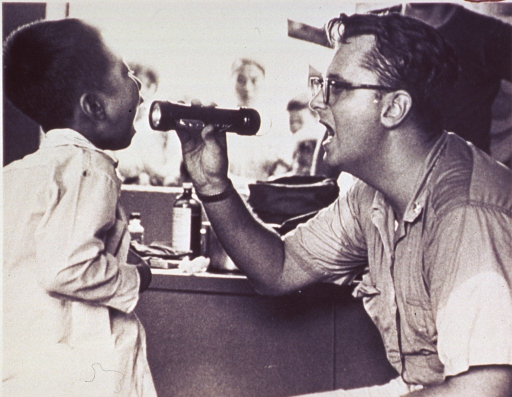 <p>Physician wearing PHS uniform, his mouth open, holds a flashlight and looks into the mouth of a young Vietnamese boy.</p>