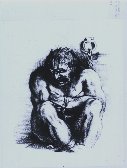 <p>A powerfully built, angry looking man is sitting on the floor, arms folded and knees are drawn up close, his head is turned to the left; his wrists and ankles are in irons which are chained to the wall.</p>