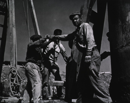 <p>Showing construction workers at a hand-operated winch.</p>